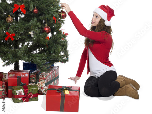 lady putting a ball decoration in christmas tree