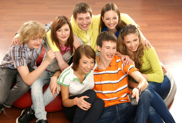 A group of young and happy teenagers watching television