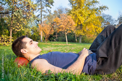 Young man  lying on a meadow grass in park