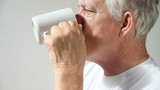 older man drinks his morning cup of coffee