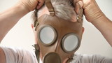 man puts on old gas mask
