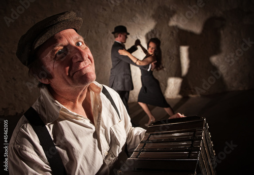 Smiling Accordion Player with Dancers