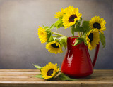 Beautiful sunflower bouquet in red jug on wooden tabletop. poster