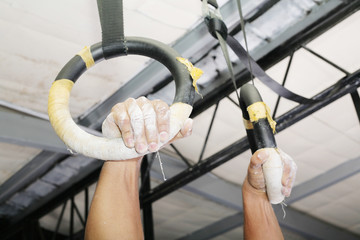 Human hanging in Gymnastic Rings. Focus on the right hand.