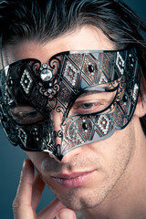 Close up portrait of young man with carnival mask