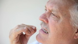 senior man cleans his teeth with a toothpick