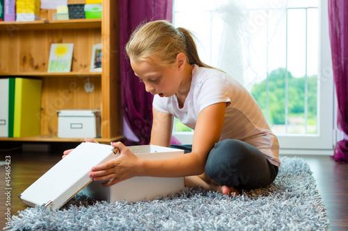 Familie - Kind oder Teenager öffnet ein Geschenk