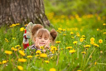 Lovely little five-year girl lying in grass