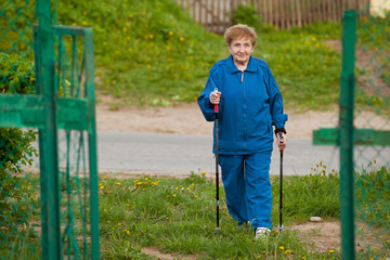 Active old woman nordic walking outdoors (85 years old) .