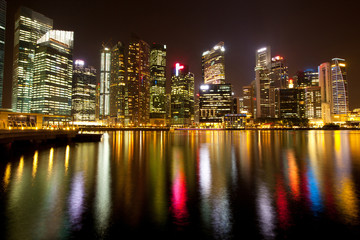 A view of Singapore district in night with water reflections.