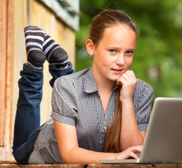 Young girl lying on the porch of the rural house with a laptop.