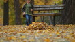 Running boy throws autumn leaves and falls to the ground