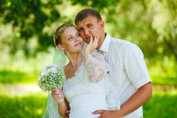 bride groom newlyweds standing in a green forest in summer at a