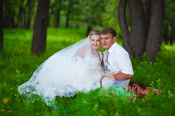 couple at wedding newlyweds picnic in a forest clearing, bride g