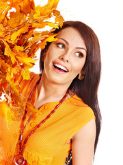 Woman holding autumn leaves .