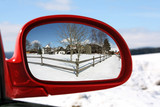 Landscape reflected in rear view mirror of a red car