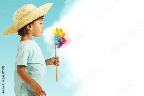 beautiful boy with straw hat having fun with wind mill