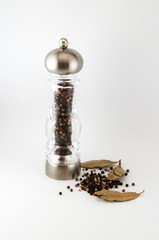 glass pepper grinder and grains of pepper and bay leaf