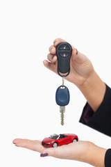 Woman holding key and small car