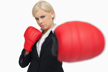 Serious businesswoman with red gloves fighting