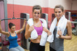 Two women with towels with woman using weight machine