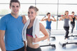 Trainer and woman smiling together while aerobics class taking p