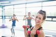 Smiling woman lifting weights while women doing aerobics