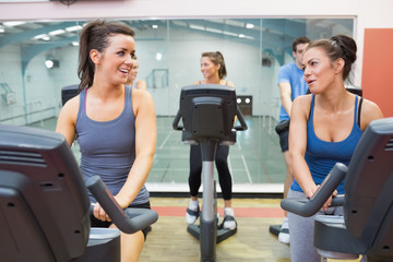 Two women talking  while training in a spinning class