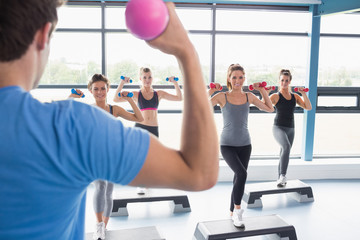 Trainer teaching his aerobics class while lifting weights