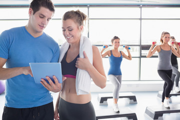 Trainer and woman talking while aerobics class lifting weights