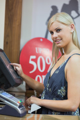 Woman is typing at the till while smiling