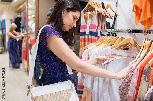 Woman with bag looking through clothes