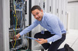 Smiling technician with tablet pc plugging cables into server