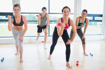 Smiling people lifting weights in aerobics class