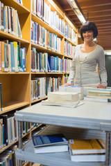 Smiling librarian pushing book trolley