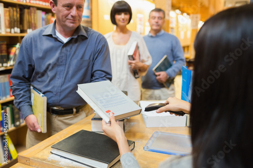 Librarian handing book to man