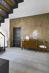 antico cassettone vicino alla porta nel soggiorno moderno