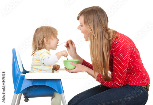 young mother feeding hungry baby in highchair