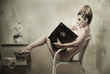 Leinwanddruck Bild - Naked woman sitting in a chair reading a book indoors