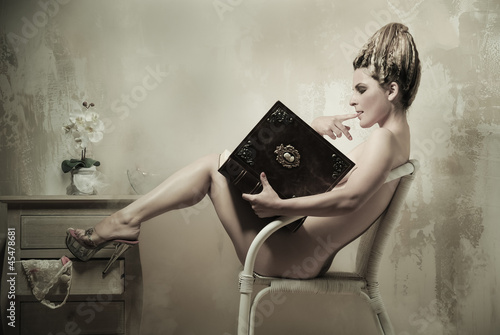 Leinwanddruck Bild Naked woman sitting in a chair reading a book indoors