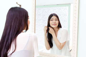 a young asian woman looking to mirror