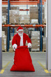 Santa Claus with large red sack in the gate to storehouse