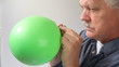 senior man deflates a green balloon