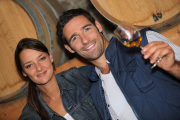 young couple tasting wine in a cellar