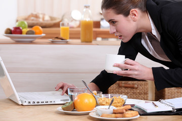 Businesswoman looking at a laptop over breakfast