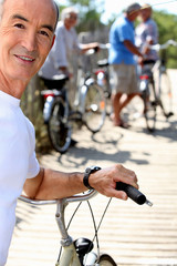 Senior man with a bicycle and his friends in the background