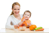 Mother spoon feeding her baby. Boy eating carrot puree