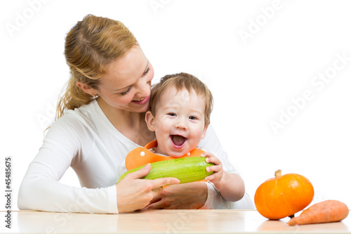 Mother with baby  baby at table. Boy holding zucchini