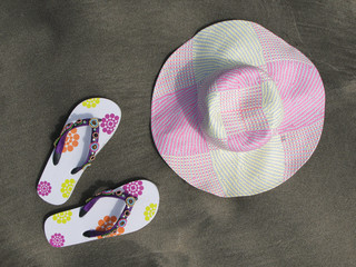 Flip-flops and hat on the black sand of Tenerife island, Canarie