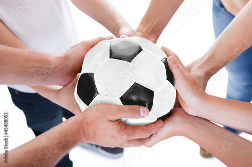 Several Hands Holding Together Soccer Ball
